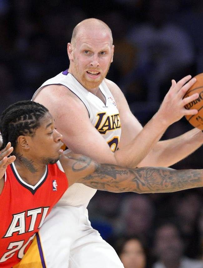 Atlanta Hawks forward Cartier Martin, center, reaches in on Los Angeles Lakers center Chris Kaman, right, as forward Elton Brand looks on during the first half of an NBA basketball game Sunday, Nov. 3, 2013, in Los Angeles