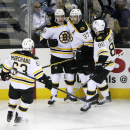 Boston Bruins right wing Reilly Smith, center left, celebrates his goal with teammates Brad Marchand (63), Patrice Bergeron (37) and Kevan Miller (86) during the first period of an NHL hockey game against the San Jose Sharks, Thursday, Dec. 4, 2014, in Sa