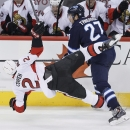 Winnipeg Jets' Eric Tangradi (27) checks Ottawa Senators' Jared Cowen (2) during the first period of an NHL hockey game, Saturday, March 8, 2014 in Winnipeg, Manitoba The Associated Press