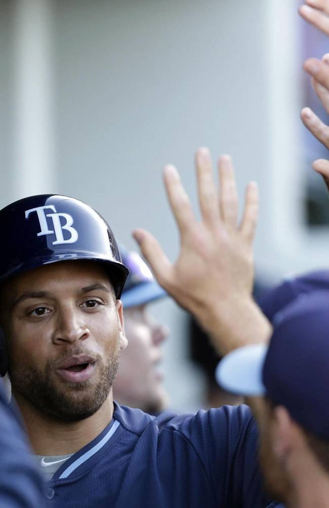 Tampa Bay Rays James Loney is greeted in the dugout after scoring on an RBI single by teammate Matt Joyce in the first inning of an exhibition baseball game against the Minnesota Twins in Fort Myers, Fla., Tuesday, March 18, 2014