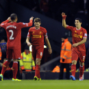 Liverpool's Luis Suarez, right, celebrates after scoring the second goal of the game with teammates Steven Gerrard, center, and Glen Johnson during their English Premier League soccer match against Norwich City at Anfield in Liverpool, England, Wednesday