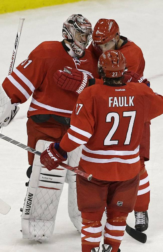 Carolina Hurricanes goalie Anton Khudobin, left, of Kazakhstan, is congratulated by teammates Andrej Sekera, of Slovakia, and Justin Faulk (27) following an NHL hockey game against the Philadelphia Flyers in Raleigh, N.C., Sunday, Oct. 6, 2013. Carolina won 2-1