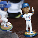 A fan places bobble-head dolls Los Angeles Dodgers' Matt Kemp, right, and Adrian Gonzalez on the field before a baseball game between the Dodgers and the Philadelphia Phillies on Wednesday, April 23, 2014, in Los Angeles The Associated Press