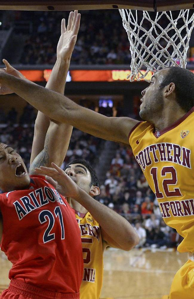 Arizona forward Brandon Ashley, left, puts up a shot as Southern California center Omar Oraby, center, and guard Julian Jacobs defend during the second half of an NCAA college basketball game, Sunday, Jan. 12, 2014, in Los Angeles
