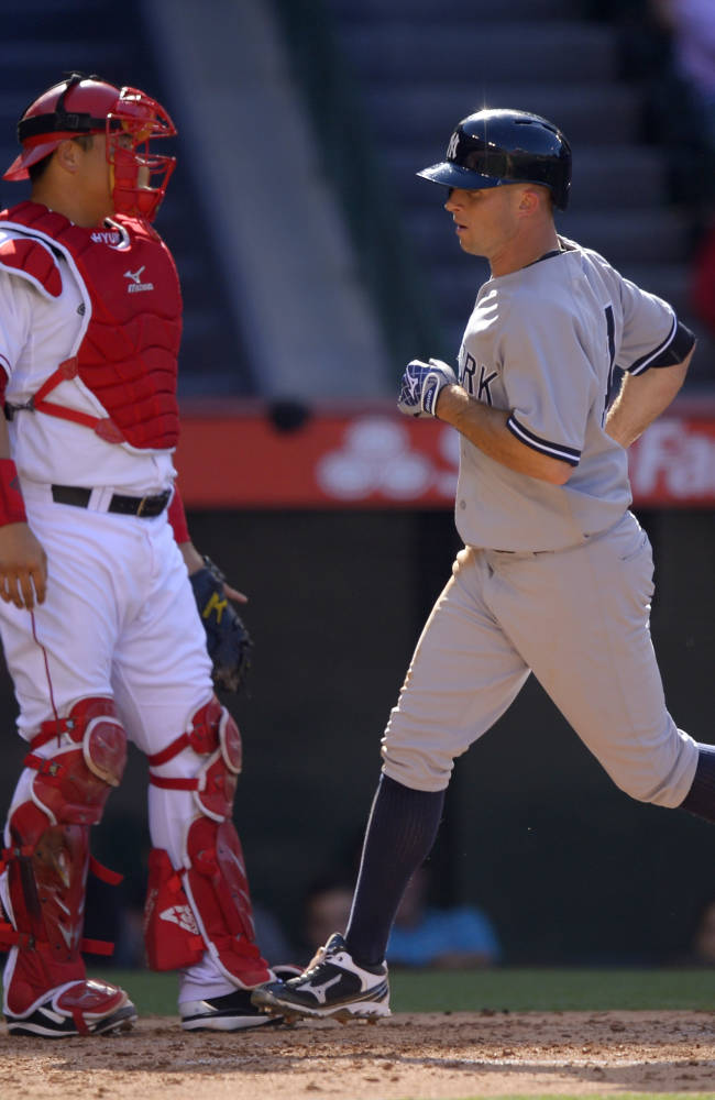 New York Yankees' Brett Gardner, right, scores on a single by Jayson Nix as Los Angeles Angels catcher Hank Conger looks on during the inning of their baseball game on Saturday, June 15, 2013, in Anaheim, Calif.  (AP Photo/Mark J. Terrill)