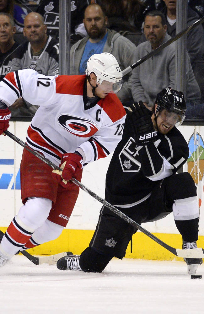 Carolina Hurricanes center Eric Staal, left, and Los Angeles Kings center Anze Kopitar, of Slovenia, vie for the puck during the second period of an NHL hockey game, Saturday, March 1, 2014, in Los Angeles