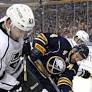Buffalo Sabres' Josh Gorges (4) battles in the corner for the puck against Los Angeles Kings' Dustin Brown (23) and Jarret Stoll (28) during the first period of an NHL hockey game Tuesday, Dec. 9, 2014, in Buffalo, N.Y The Associated Press