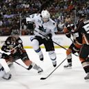 San Jose Sharks' Logan Couture, center, jumps out of the way as Jason Demers, left, tries to score against Anaheim Ducks goalie John Gibson during the first period of an NHL hockey game Wednesday, April 9, 2014, in Anaheim, Calif The Associated Press