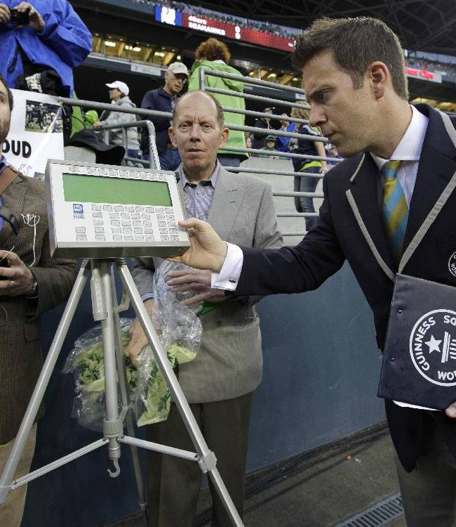 Philip Robertson, right, an adjudicator with Guinness World Records, examines a device used to measure the sound level of cheering fans at CenturyLink Field in Seattle prior to an NFL football game between the Seattle Seahawks and the San Francisco 49ers, Sunday, Sept. 15, 2013, in Seattle. Fans are at the notoriously loud stadium are attempting to set a new Guinness World Record for crowd noise at an athletic event during the game. At left is Matt Roe, an acoustical consultant with Seattle-based SSA Acoustics who will be measuring the sound levels