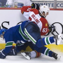 Vancouver Canucks right wing Radim Vrbata goes into the boards with Florida Panthers center Dave Bolland (63) during the second period of an NHL hockey game Thursday, Jan. 8, 2015, in Vancouver, British Columbia The Associated Press