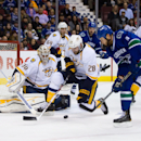 Vancouver Canucks' Zack Kassian, right, attempts a shot against Nashville Predators goalie Carter Hutton, left, as Paul Gaustad, center, defends and Victor Bartley (64) and Seth Jones (3) watch during first-period NHL hockey game action in Vancouver, Brit