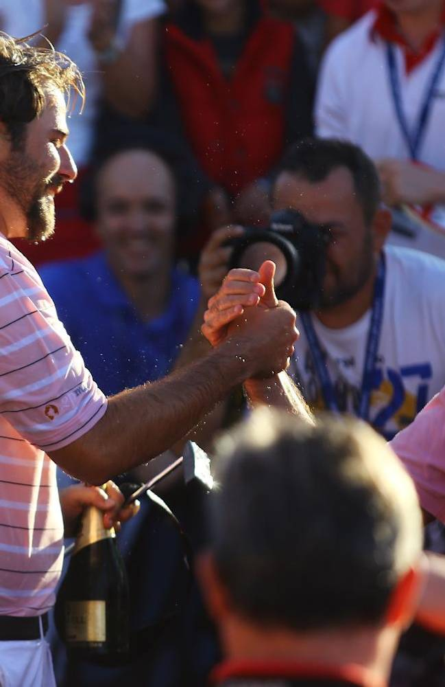 Victor Dubuisson of France, left, is congratulated by friends after his victory in the Turkish Open golf tournament at the Montgomerie Maxx Royal Course in Antalya, Turkey, Sunday, Nov. 10, 2013