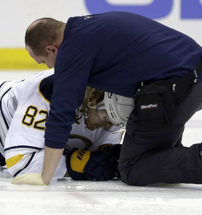 Buffalo Sabres' Marcus Foligno (83) is tended to by a trainer after being injured during the first period of an NHL hockey game against the St. Louis Blues, Thursday, April 3, 2014, in St. Louis