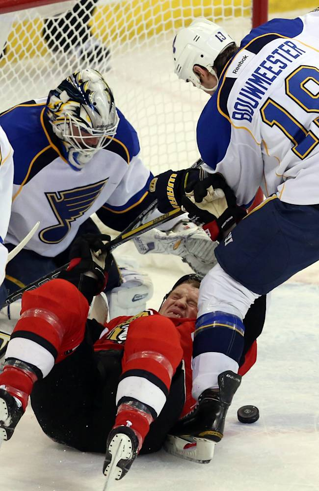 Ottawa Senators Chris Neil (25) is checked by St. Louis Blues Jay Bouwmeester (19) as Blues goaltender Brian Elliot (1) looks for the puck during first period, NHL hockey between the Ottawa Senators and the St Louis Blues in Ottawa Monday,  Dec. 16, 2013