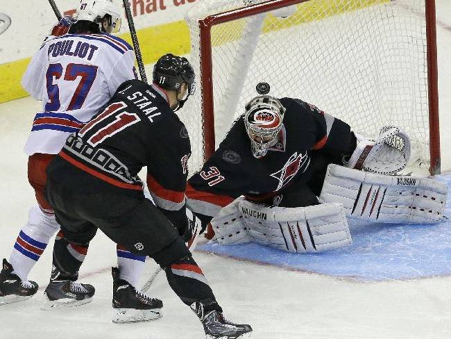Carolina Hurricanes' Jordan Staal (11) and goalie Anton Khudobin (31), of Kazakhstan, defend the goal from New York Rangers' Benoit Pouliot (67) during the third period of an NHL hockey game in Raleigh, N.C., Friday, March 7, 2014. New York won 4-2