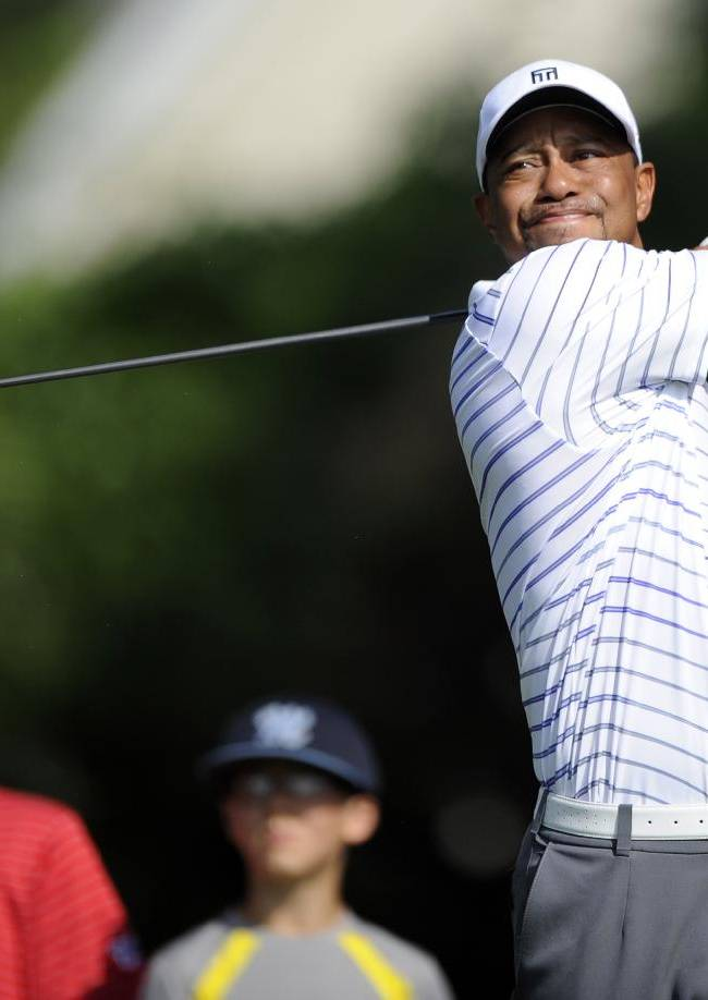 Tiger Woods watches his tee shot on the third hole during the Pro-Am at the Quicken Loans National golf tournament, Wednesday, June 25, 2014, in Bethesda, Md
