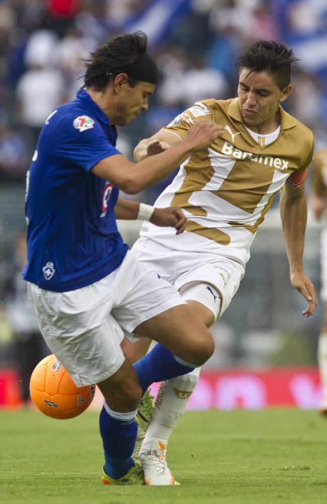 Pumas Efrain Velarde, right, fights for the ball with Cruz Azuls Gerardo Flores during a Mexican soccer league match in Mexico City, Saturday, April  26, 2014