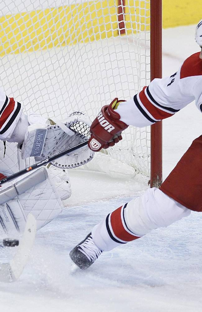Carolina Hurricanes goaltender Cam Ward (30) stops a Winnipeg Jets shot as Jay Harrison (44) helps defend during the first period of an NHL hockey game, Saturday, March 22, 2014, in Winnipeg, Manitoba