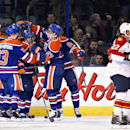 Florida Panthers Mike Mottau (22) skates past as Edmonton Oilers Ryan Nugent-Hopkins (93), Taylor Hall (4), Jordan Eberle (14), David Perron (57) and Nail Yakupov (64) celebrate a goal during first period NHL hockey action in Edmonton, Alberta, on Thursda