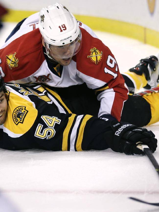 Boston Bruins defenseman Adam McQuaid (54) tries to knock the puck free as he is dropped to the ice by Florida Panthers right wing Scottie Upshall (19) during the first period of an NHL hockey game, Thursday, Nov. 7, 2013, in Boston