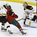 Boston Bruins goalie Tuukka Rask (40), of Finland, deflects a shot by Minnesota Wild center Stephane Veilleux, center, past Bruins center Carl Soderberg (34) during the first period of an NHL hockey game in St. Paul, Minn., Tuesday, April 8, 2014 The Asso
