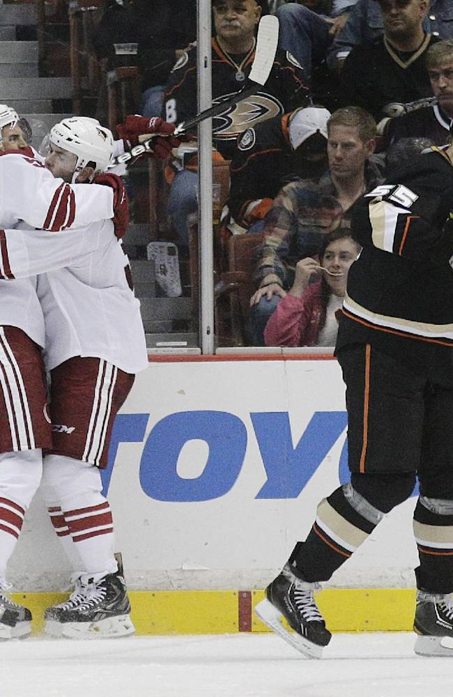 Phoenix Coyotes' Antoine Vermette, left, celebrates his goal with Keith Yandle as Anaheim Ducks' Bryan Allen, right, skates away during the second period of an NHL hockey game on Friday, Oct. 18, 2013, in  Anaheim, Calif