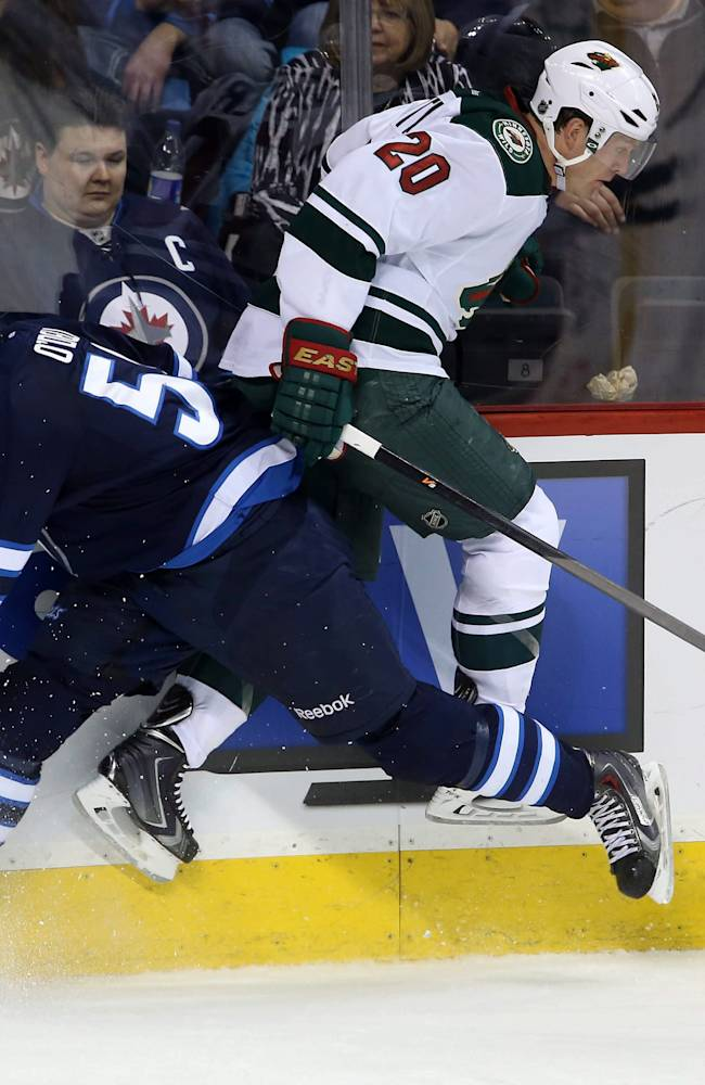 Winnipeg Jets' Eric O'Dell (58) collides with Minnesota Wild's Ryan Suter (20) during third period NHL hockey action in Winnipeg, Manitoba, Monday, April 7, 2014
