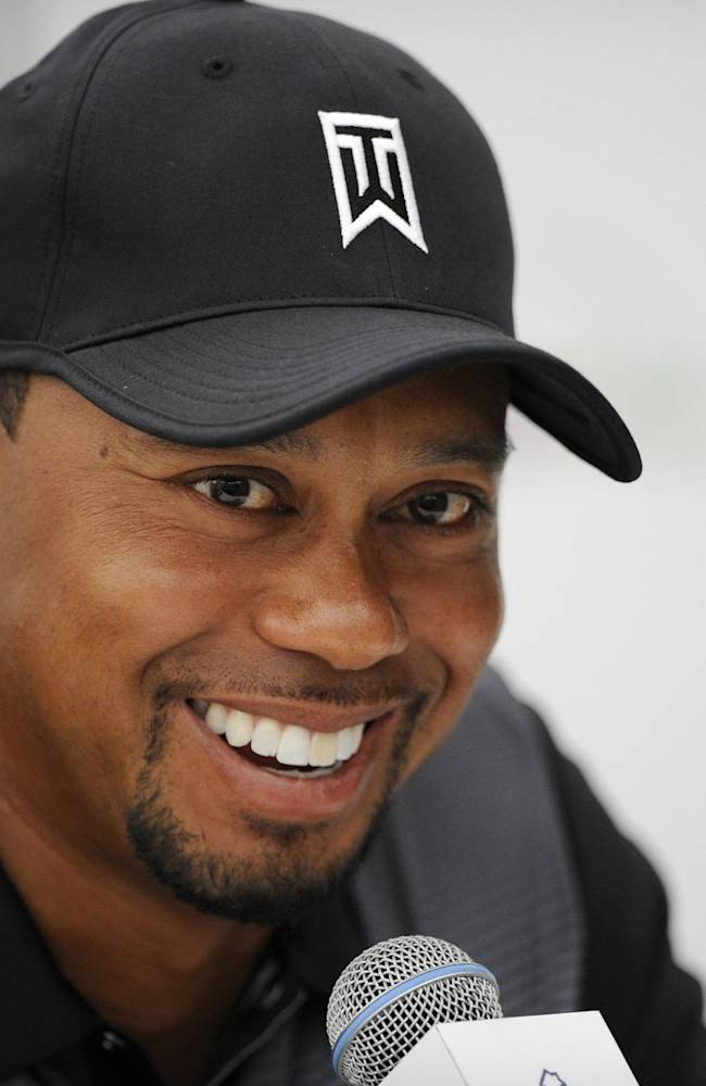 Tiger Woods smiles at a press conference at the Quicken Loans National golf tournament, Tuesday, June 24, 2014, in Bethesda, Md