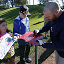 Atlanta Braves catcher Ryan Doumit signs an autograph for a fan during a spring training baseball workout on Sunday, Feb. 16, 2014, in Kissimmee, Fla The Associated Press