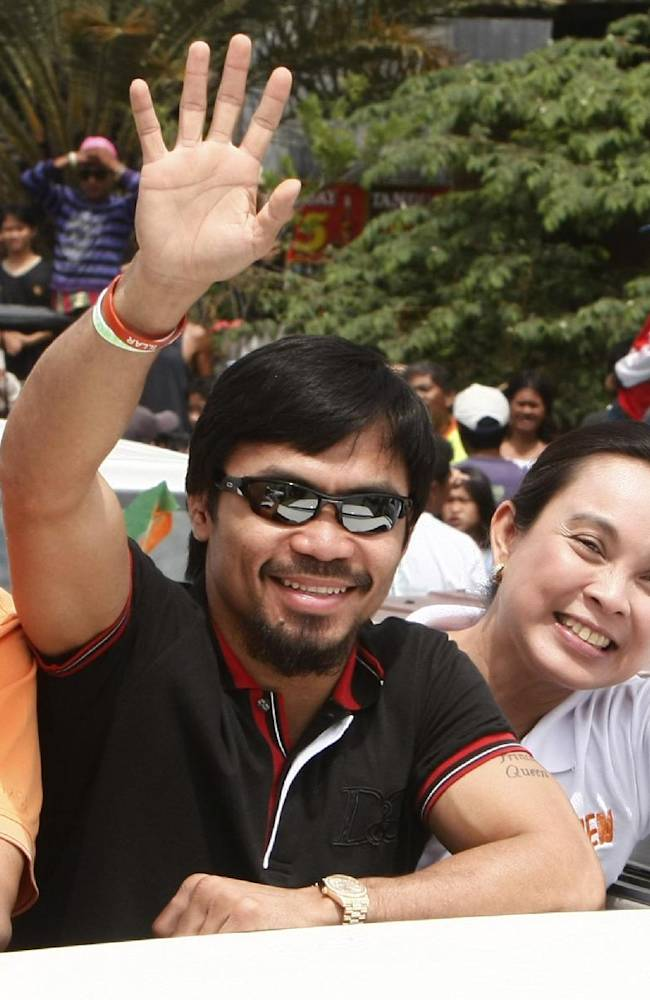 In this March 26, 2010 file photo, Filipino boxing great Manny Pacquiao waves from a vehicle at his election campaign during a motorcade sortie from General Santos city to Sarangani province in southern Philippines. Pacquiao is dedicating his comeback fight against Brandon Rios to the victims of the devastating typhoon that has left hundreds of thousands displaced in his native Philippines. The eight-division champion is in camp in the southern Philippines - only about 320 kilometers (200 miles) from where Typhoon Haiyan caused the most destruction - for the Nov. 24, 2013 bout in Macau