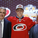 Haydn Fleury stands with Carolina Hurricanes officials after being chosen seventh overall during the first round of the NHL hockey draft, Friday, June 27, 2014, in Philadelphia The Associated Press