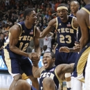 Georgia Tech's Marcus Georges-Hunt, on ground, celebrates with teammates Stacey Poole Jr. (12) and Brandon Reed (23) after Tech's game-winning basket during an NCAA college basketball game against Miami in Coral Gables, Fla., Wednesday, March 6, 2013. Georgia Tech won 71-69. (AP Photo/Luis M. Alvarez)