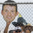 Fan Arnold Gomez of San Diego, with his daughter Victoria, holds a picture of Dallas Cowboys quarterback Tony Romo at NFL football training camp, Wednesday, July 30, 2014, in Oxnard, Calif The Associated Press