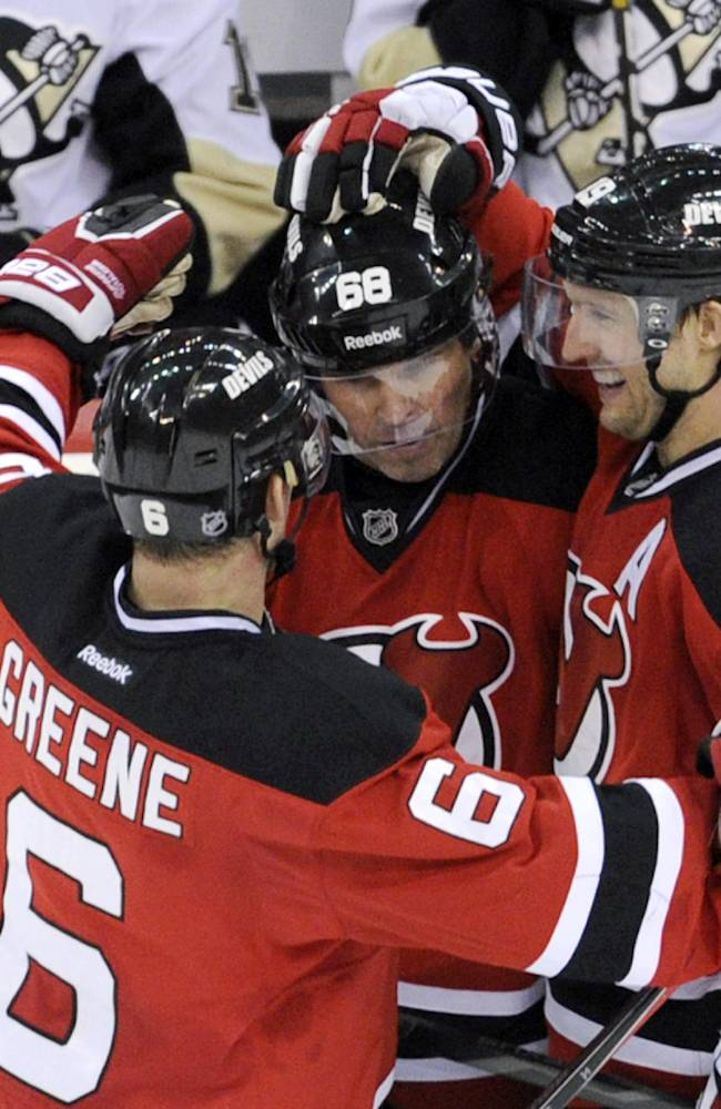 New Jersey Devils' Jaromir Jagr, of Czech Republic, celebrates his unassisted empty-net goal with Andy Greene, left, and Travis Zajac, right, during the third period of an NHL hockey game against the Pittsburgh Penguins, Saturday, Nov. 16, 2013, in Newark, N.J.  The Devils won 4-1