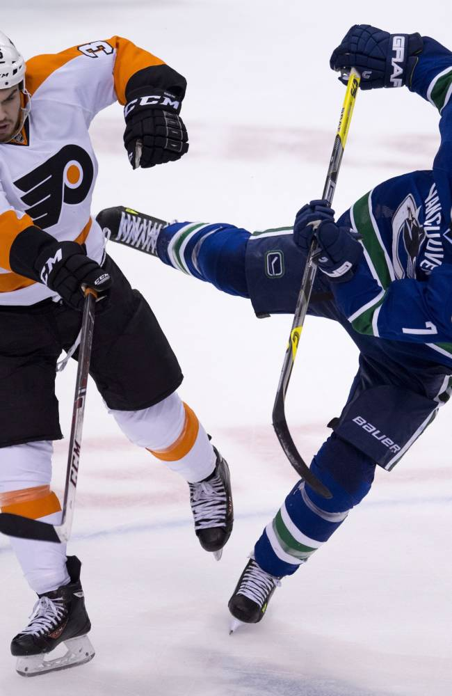 Vancouver Canucks left wing David Booth (7) and Philadelphia Flyers centre Zac Rinaldo (36) fight for control of the puck during the third period of NHL action in Vancouver, British Columbia Monday, Dec. 30, 2013