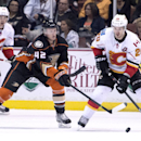 Anaheim Ducks' Josh Manson, left, reaches out for the puck with Calgary Flames' Curtis Glencross during an NHL hockey game Tuesday, Nov. 25, 2014, in Anaheim, Calif The Associated Press