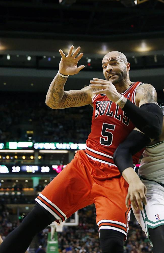 The ball goes out of bounds as Chicago Bulls' Carlos Boozer (5) and Boston Celtics' Jared Sullinger (7) battle for a rebound in the first quarter of an NBA basketball game in Boston, Sunday, March 30, 2014