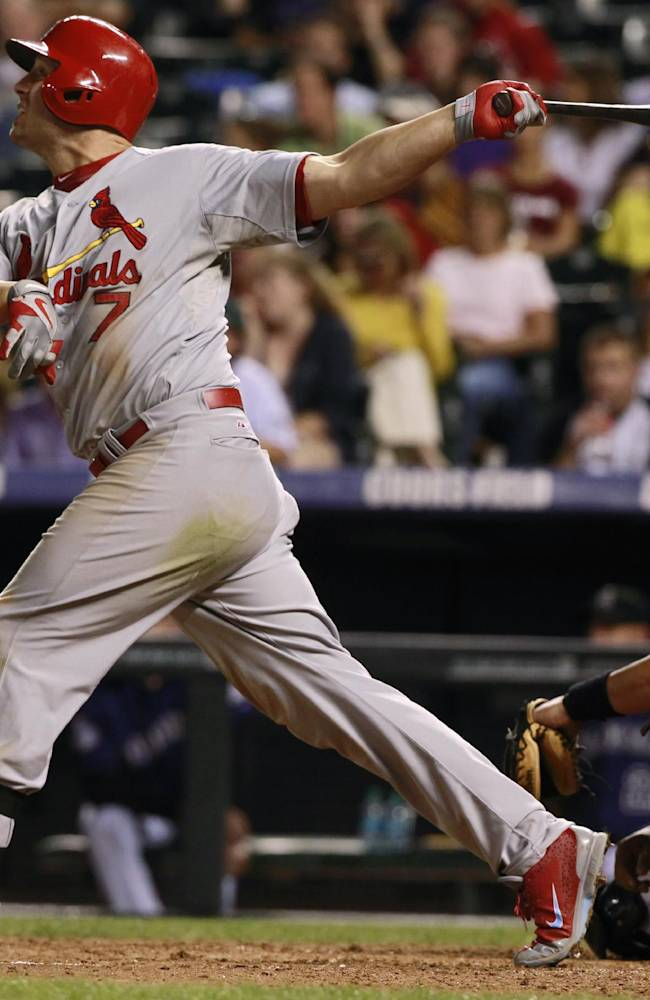 St. Louis Cardinals' Matt Holliday, left, folows the flight of his two-run home run with Colorado Rockies catcher Yorvit Torrealba in the fifth inning of the Cardinals' 11-4 victory in a baseball game in Denver on Tuesday, Sept. 17, 2013