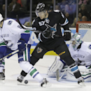 Vancouver Canucks' Chris Tanev (8) and goalie Ryan Miller, right, defend against San Jose Sharks' Tommy Wingels (57) during the third period of an NHL hockey game Thursday, Nov. 6, 2014, in San Jose, Calif. Vancouver won, 3-2 The Associated Press