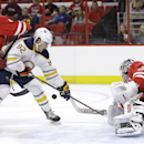 Carolina Hurricanes' Jay Harrison, left, defends Buffalo Sabres' Marcus Foligno (82) as Hurricanes goalie Cam Ward (30) protects the goal during the first period of a preseason NHL hockey game in Raleigh, N.C., Friday, Oct. 3, 2014 The Associated Press
