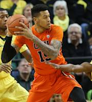 Oregon's Mike Moser, left, and Johnathan Lyod, right, pressure Oregon State's Eric Moreland under the basket during the first half of an NCAA college basketball game in Eugene, Ore., Sunday, Feb. 16, 2014. (AP Photo/Chris Pietsch)