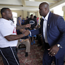 Carolina Panthers' Mike Tolbert, left, congratulates former teammate Travelle Wharton after Wharton's retirement announcement at the team's training camp in Spartanburg, S.C., Tuesday, July 29, 2014 The Associated Press