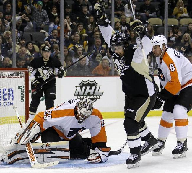 Pittsburgh Penguins' Sidney Crosby (87) celebrates his second-period goal between Philadelphia Flyers goalie Ray Emery (29) and Nicklas Grossmann (8) during an NHL hockey game in Pittsburgh, Wednesday, Nov. 13, 2013