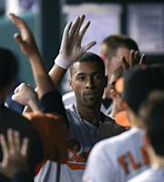 Baltimore Orioles' Henry Urrutia, center, is congratulated by teammates after scoring on a double by Brian Roberts in the fifth inning during a baseball game against the Kansas City Royals, Thursday, July 25, 2013, in Kansas City, Mo. (AP Photo/Ed Zurga)