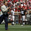 Coach Nick Saban cheers after the white team scored a touchdown during Alabama's spring NCAA college football game in Tuscaloosa, Ala. on Saturday, April 20, 2013. (AP Photo/Butch Dill)