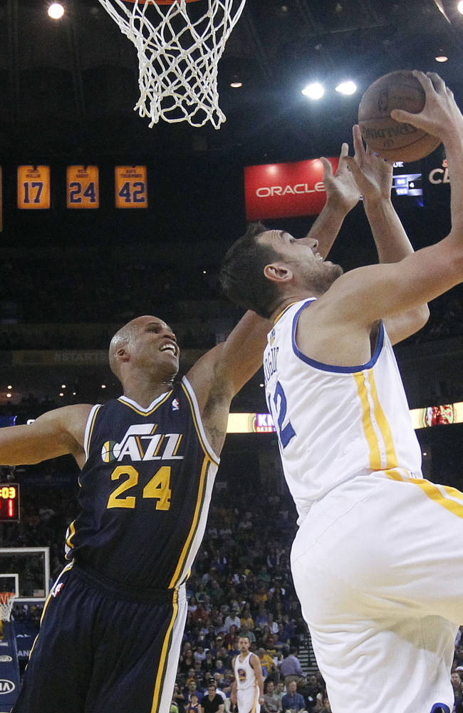 Golden State Warriors center Andrew Bogut, right, shoots next to Utah Jazz forward Richard Jefferson (24) during the first half of an NBA basketball game Sunday, April 6, 2014, in Oakland, Calif