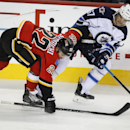 Winnipeg Jets' Michael Frolik, right, from the Czech Republic, battles with Calgary Flames' Devin Setoguchi during the first period of an NHL pre-season hockey game, Thursday, Oct. 2, 2014 in Calgary, Alberta The Associated Press