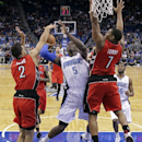 Orlando Magic's Victor Oladipo (5) shot is blocked by Toronto Raptors forward Landry Fields (2) as Kyle Lowry (7) comes in to help during the first half of an NBA basketball game in Orlando, Fla., Sunday, March 30, 2014 The Associated Press
