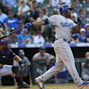 Los Angeles Dodgers' Carl Crawford, right, follows the flight of his RBI-double with Colorado Rockies catcher Wilin Rosario in the ninth inning of the Dodgers' 10-8 victory in a baseball game in Denver on Monday, Sept. 2, 2013. (AP Photo/David Zalubowski)