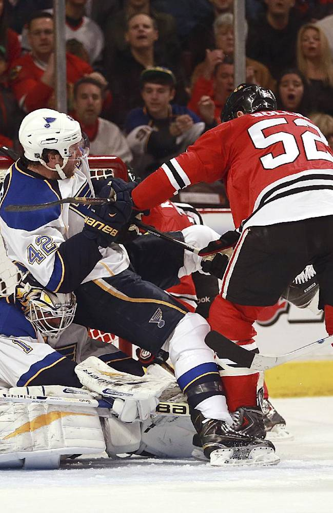 Chicago Blackhawks Brandon Bollig (52) and St Louis Blues' David Backes wrestle in front of the Blues goalie Brian Elliot, left, during the first period of an NHL hockey game in Chicago on Sunday, April 6, 2014